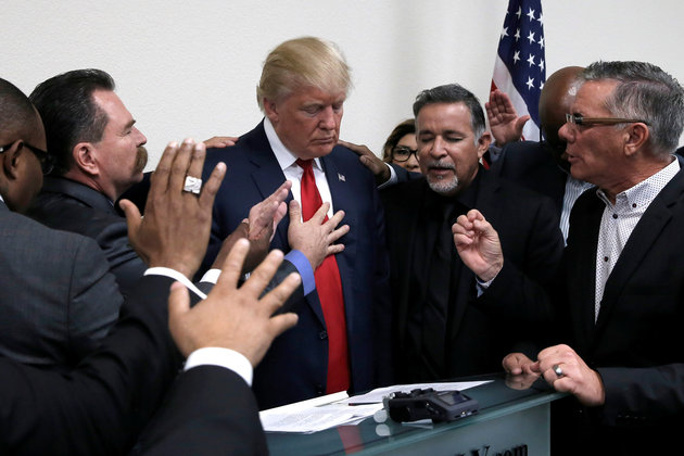 Republican presidential nominee Donald Trump prays with pastors during a campaign visit to the International Church of Las Vegas